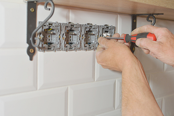 An image showing an electrician installing a power socket in a bathroom